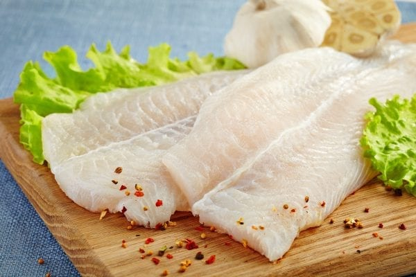 fresh raw pangasius fish fillet on wooden cutting board